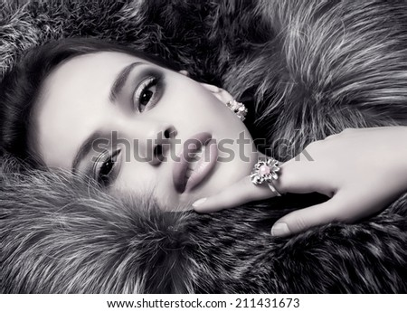 Portrait of beautiful young woman with makeup and precious decorations - stock photo
