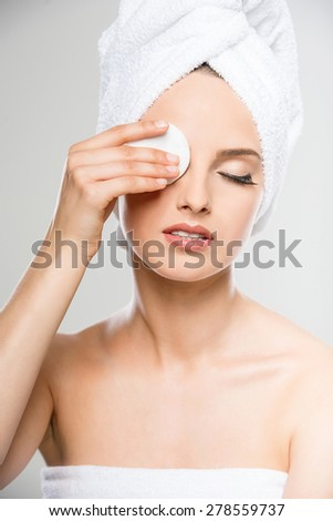 Portrait of beautiful young woman with towel cleaning skin with cotton swab. - stock photo
