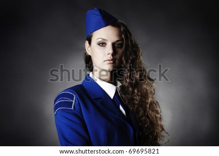 portrait of beautiful young woman with uniforme black background studio photo - stock photo