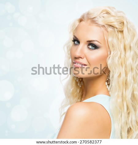 Portrait of beautiful young woman with wavy long blond hair and bright makeup. Isolated. Copy space - stock photo