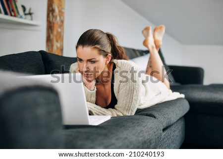 Portrait of beautiful young woman working on laptop while lying on sofa. Female using laptop at home. - stock photo
