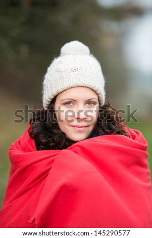 Portrait of beautiful young woman wrapped in shawl at park - stock photo