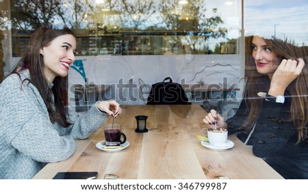 Portrait of beautiful young women drinking tea in a coffee shop. - stock photo
