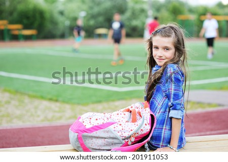 Portrait of beauty pre-teen tween kid girl with long brunette hair watching soccer game on the school soccer field - stock photo