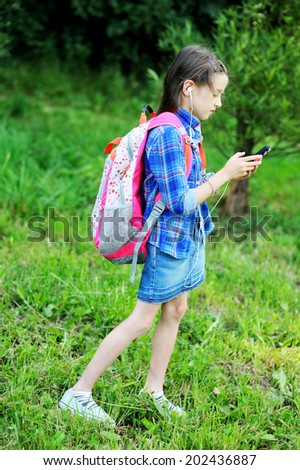 Portrait of beauty pre-teen tween kid girl with long brunette hair wearing pink  rucksack with headphones listening to music outside  - stock photo