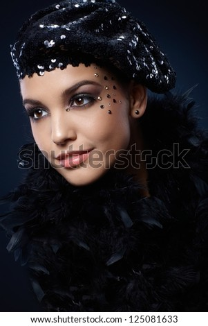 Portrait of beauty smiling in black sequin party hat and boa, with glamorous makeup of rhinestones. - stock photo