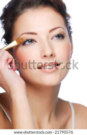 Portrait of beauty young caucasian woman applying eyeshadow on eyelid - stock photo