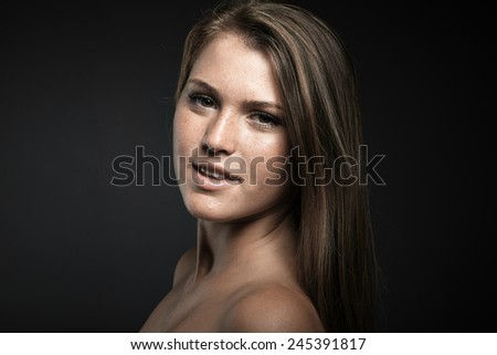 Portrait of beauty young woman against dark grey background - stock photo