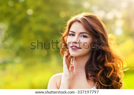 Portrait of beauty young woman with long hair in the sunlight - stock photo