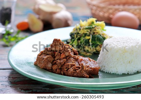 portrait of beef rendang served with  urap and rice - stock photo