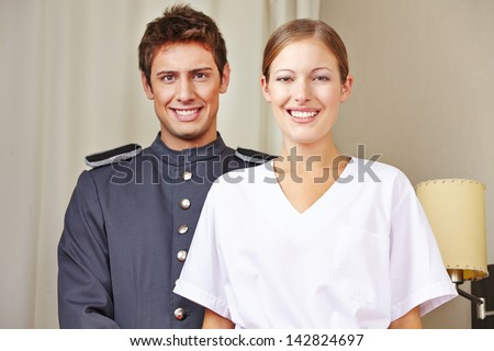 Portrait of bellboy and hotel maid in a hotel room - stock photo