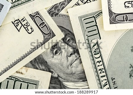 portrait of Benjamin Franklin on the hundred dollar bill framed by other banknotes - stock photo