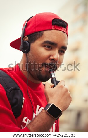 Portrait of black boy using modern e-cig vaporizer device for smoking glycerine liquid tobacco with flavor. Popular gadget among young people and who want to improve health and quit smoking - stock photo