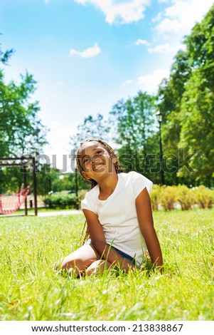 Portrait of black girl in park dreaming on lawn - stock photo