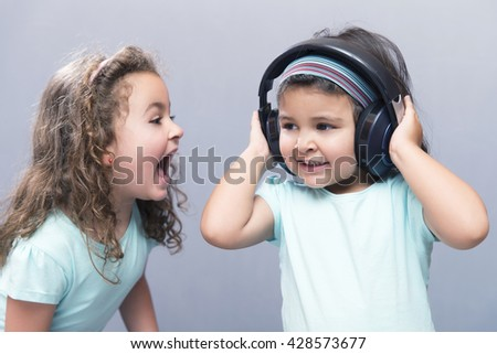 Portrait of black-haired girl in headphones with older sister screaming - stock photo