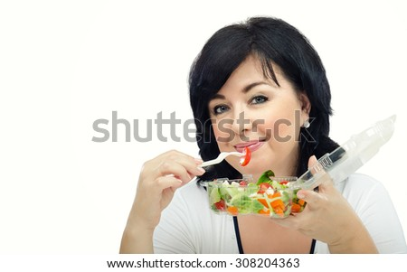 Portrait of black haired woman with takeaway salad. She is holding a plastic transparent container with vegetable salad by left hand. In right hand, she is clasping white fork with small cherry tomato - stock photo
