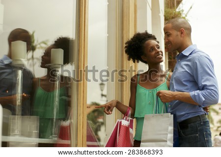Portrait of black tourist heterosexual couple in Panama City with shopping bags. The man and his girlfriend look at shop window - stock photo
