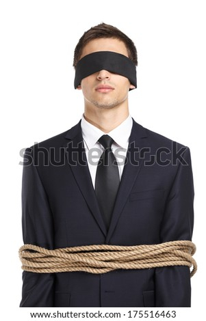 Portrait of  blind-folded businessman tied with the rope, isolated on white. Concept of slavery and violence - stock photo