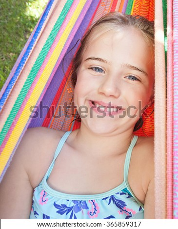 Portrait of blond child girl with blue eyes looking at camera and smiling, relaxing on a colorful hammock in a home garden on summer holiday in swimming costume. Vacation lifestyle kid fun activities. - stock photo