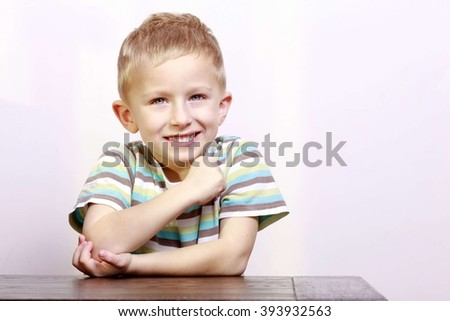 Portrait of blond cute happy laughing boy child kid at the table interior. Emotions and fun. - stock photo