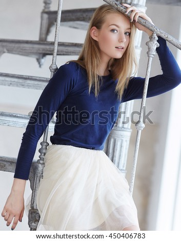 Portrait of blond female in a white skirt on a ladder. - stock photo