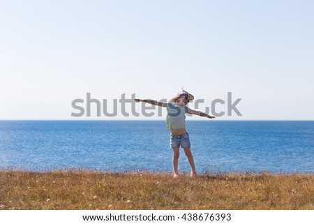 portrait of blond girl in preschool age standing on dried grass field with sea on background and holding hands wide aside  - stock photo
