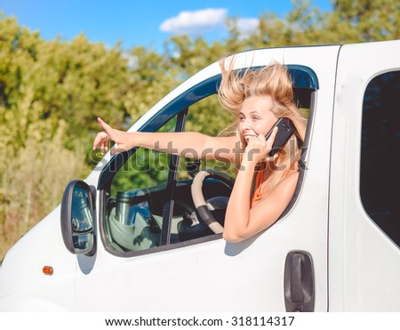 Portrait of blond girl in white car speaking by phone and looking from car window. Young woman excited and smiling while talking with someone and pointing up on summer countryside background. - stock photo
