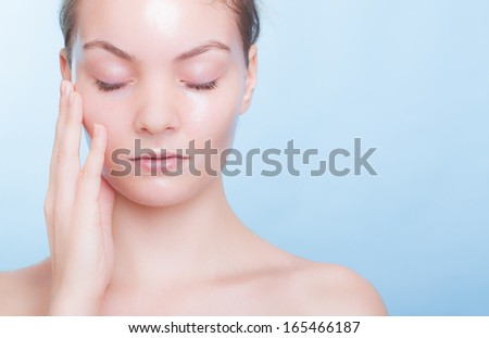 Portrait of blond girl young woman in facial peel off mask. Peeling. Beauty body skin care. Blue background. Studio shot. - stock photo