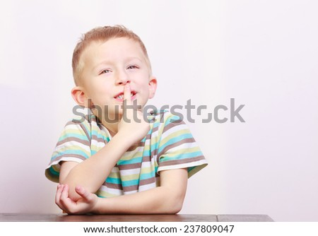 Portrait of blond pensive thoughtful boy or child kid asking for quiet with finger on lips at the table interior. Emotions. Copyspace. - stock photo