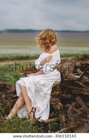 portrait of blond woman in white dress outdoor. closeup of beautiful girl in long white dress outdoors.blonde beautiful woman - stock photo