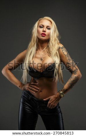 Portrait of blond woman. Studio shoot. Isolated on grey - stock photo