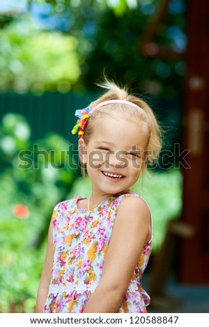 Portrait of blonde beautiful smiling little girl close-up, against background of summer park. - stock photo