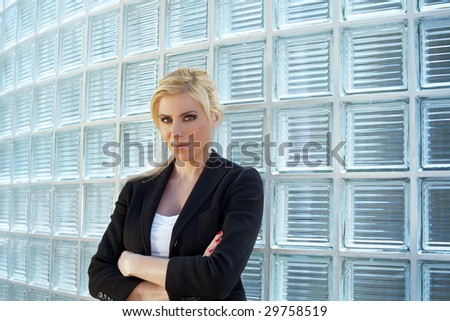 portrait of blonde businesswoman with arms folded looking at camera. Copy space - stock photo