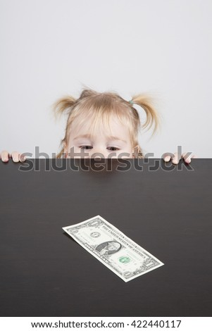 portrait of blonde caucasian baby nineteen month age with pigtails chubby face yellow shirt looking at dollar banknote on brown table vertical - stock photo