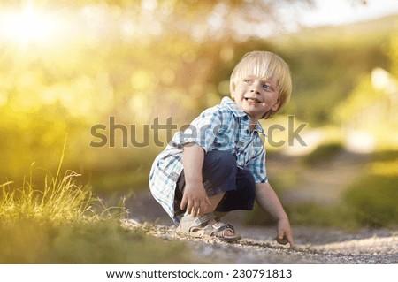 Portrait of blonde little boy posing outside - stock photo