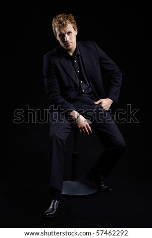 portrait of blonde man in black suit sitting on chair on black - stock photo