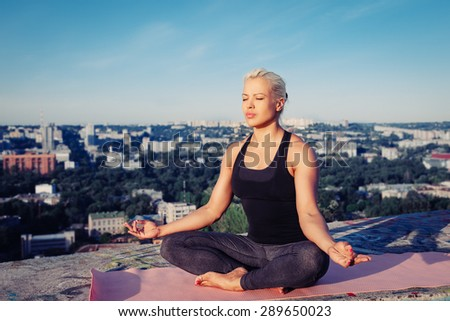 Portrait of blonde strong woman in sportwear doing workout on the roof of skyscraper above the big city at early morning. Female sporty muscular body. Dawn and sunrise bright sunny light.  - stock photo