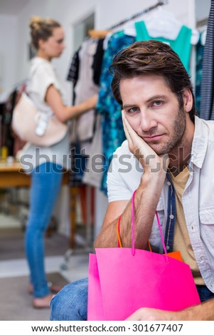 Portrait of bored man with shopping bags sitting in front of his girlfriend in clothing store - stock photo