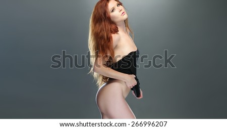 Portrait of Bottomless Seductive Young Woman Posing in Black Tube Tops Only While Looking at the Camera on a Gray Background. - stock photo