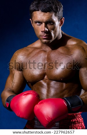 Portrait of boxer posing in studio in gloves. - stock photo