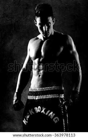 Portrait of boxer posing in studio in gloves. Fine art. - stock photo