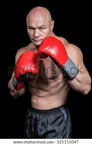 Portrait of boxer with gloves against black background - stock photo
