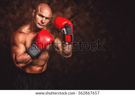 Portrait of boxer with red gloves against dark background - stock photo