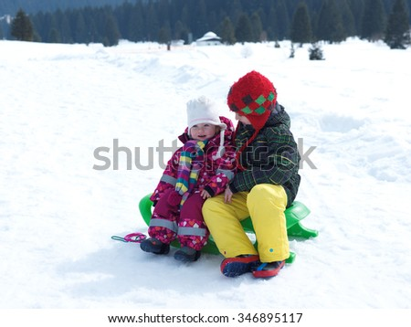 portrait of boy and baby girl on winter vacation sitting on sleddge with fresh snow on beautiful sunny day - stock photo