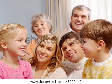 Portrait of boy and girl looking at each other with their parents and grandparents on background - stock photo