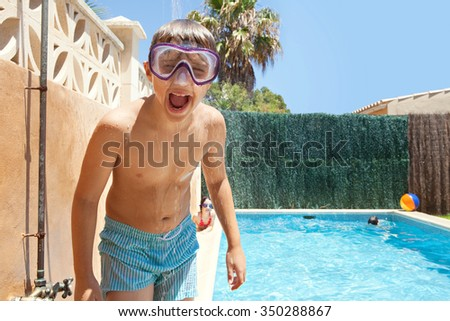Portrait of boy child under a shower having fun in swimming pool home garden on a sunny summer holiday, outdoors. Active kids lifestyle, pulling faces wearing diving mask, house exterior vacation. - stock photo