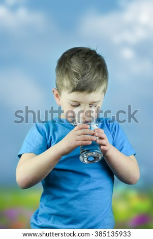 Portrait of boy drinking glass of water - stock photo