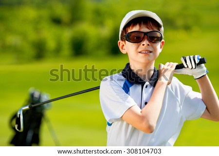 Portrait of boy golfer in golf course at summer day - stock photo