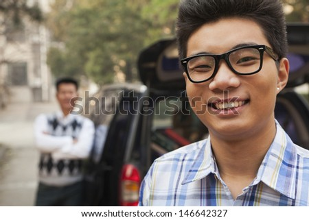 Portrait of boy in front of car on college campus - stock photo