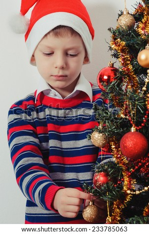 Portrait of boy in Santa red hat decorating Christmas tree with baubles - stock photo